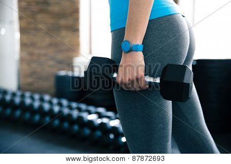 Closeup image of a woman holding dumbbells at gym