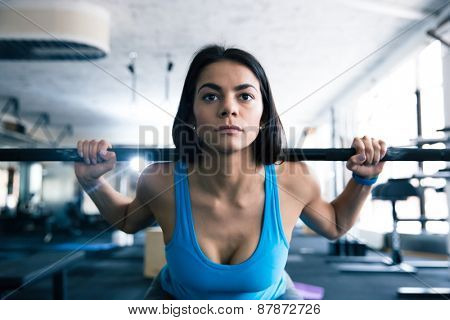 Attractive young woman working out with barbell at gym