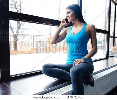 Happy fit woman talking on the phone and looking on window