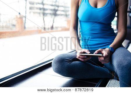 Closeup image of a woman using smartphone near window