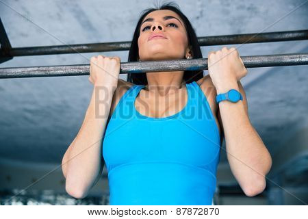 Beautiful fit woman working out on horizontal bar at gym