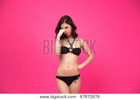 Young woman in black bikini covering her nose over pink background