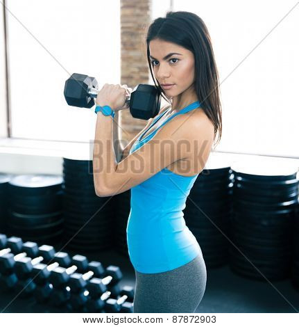 Woman working out with dumbbells at gym