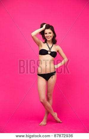 Young smiling beautiful woman posing in black bikini over pink background. Looking at camera