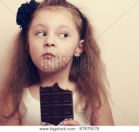 Thinking Expression Kid Girl Eating Chocolate. Closeup Vintage