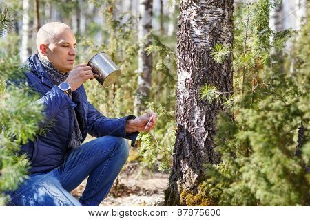 man in forest drinking from  cup tree sap