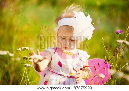 Beautiful Carefree Girl Playing Outdoors In Field With High Green Grass