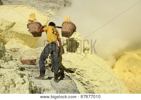 KAWAH IJEN, INDONESIA - AUGUST 8, 2011: Miner carries baskets with sulphur in clouds of toxic volcanic gas at the sulphur mines in the crater of the active volcano of Kawah Ijen, East Java, Indonesia.