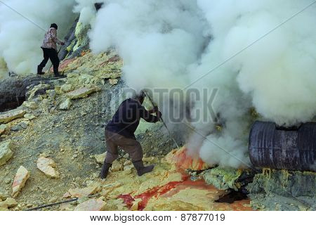 KAWAH IJEN, INDONESIA - AUGUST 9, 2011: Miners collect sulphur in the fumes of toxic volcanic gas at s the ulphur mines in the crater of the active volcano of Kawah Ijen, East Java, Indonesia.