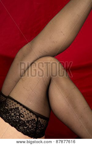 Womans Legs Up Close In Black Stockings On Red