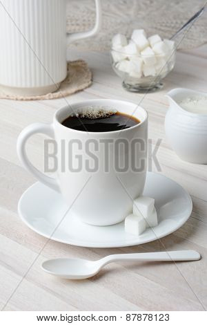 Coffee Mug Still Life. Vertical format shot of a white mug of coffee on a white wood table surrounded by white accessories.