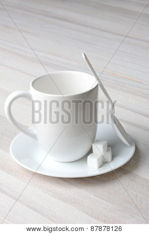 Closeup of a white coffee mug white plastic spoon and white sugar cubes on a rustic whitewashed kitchen table. Vertical format with copy space.