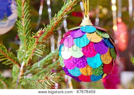 Multicolored Christmas Ball On Spruce Branch.