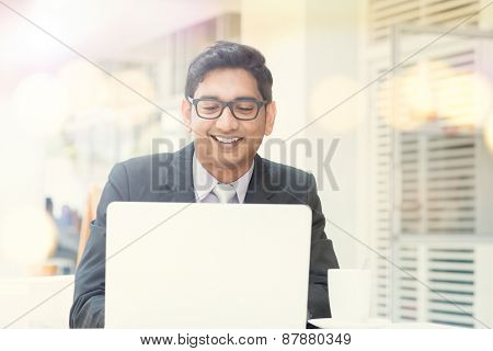 Businessman at cafeteria, having a cup of coffee and using internet.