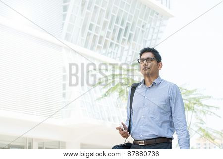 Young business man walking by a modern office building.
