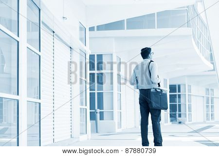Young businessman walking through a modern office building.