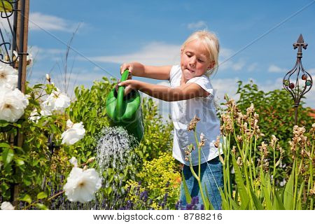 Little girl watering the flowers