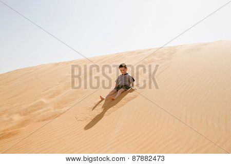 Little boy enjoys the warm sand sitting on a dune