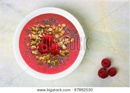 Smoothie bowl with raspberries, superfoods on white granite