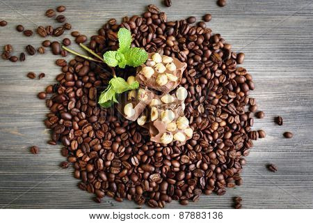 Chocolate with mint and coffee beans on wooden table, top view