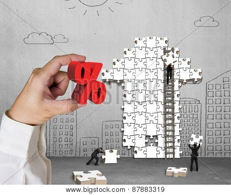 Hand Holding Percentage Sign With Businessmen Building Arrow Puzzle