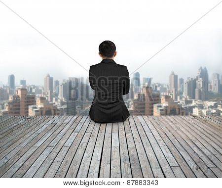 Rear View Businessman Sitting On Wooden Floor With Urban Scene