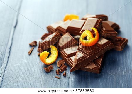 Pieces of chocolate with orange peels on wooden background
