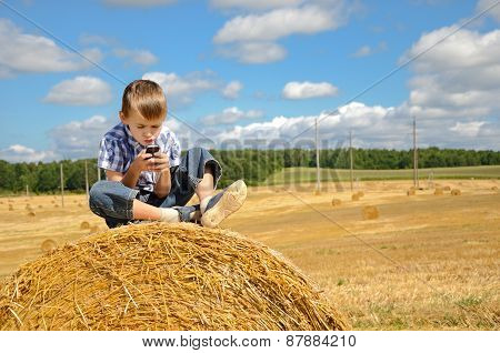 Young Boy Sitting On Haystack With Phone