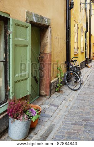 Fragment of paved Swedish streets with flowers by the window, door and the cycle