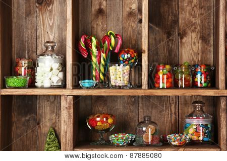 Colorful candies in jars on wooden shelves  close-up