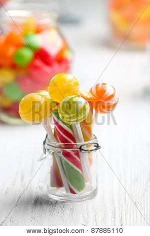 Colorful candies in jars on table on light background background