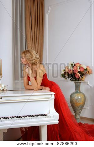 A Woman Dressed In Red Long Dress Leaning Over White Piano In Thought