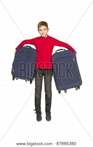 Happy boy jumping near travel bag isolated on white
