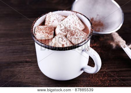 Mug of cocoa with marshmallows on wooden background