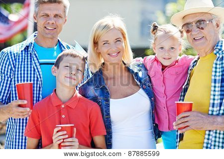 Happy senior man with his children and grandchildren looking at camera