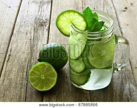 Detox water with lime and cucumbers on wood background