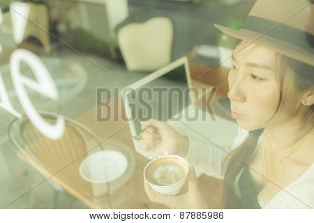 Blurred Asian Woman Drinking Coffee And Using Computer In Cafe.