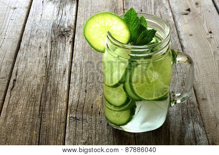 Detox water with lime and cucumbers on aged wood
