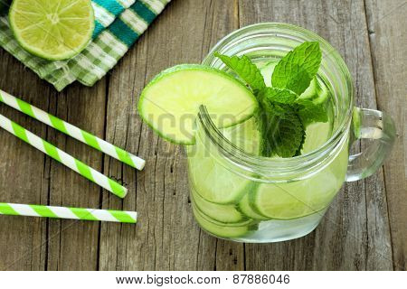 Detox water with lime and cucumbers above view in jar