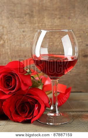 Composition with red wine in glass, red roses and decorative heart on wooden background