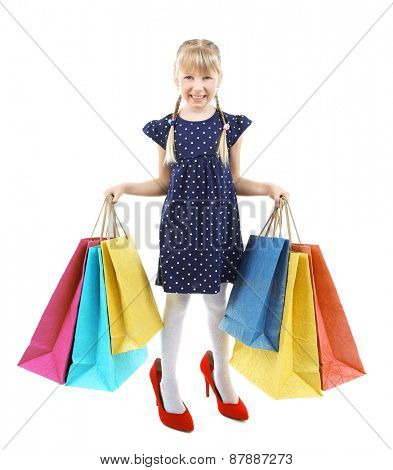 Beautiful little girl in mommy's  shoes with shopping bags isolated on white