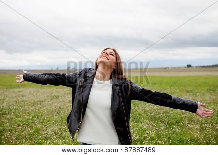 Beautiful woman with leather jacket relaxing in the countryside surrounded by flowers