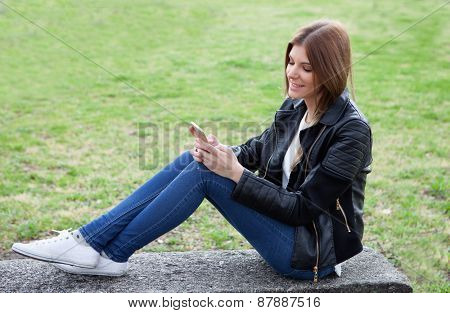 Cool pretty woman with the mobile sitting on a bank at the park