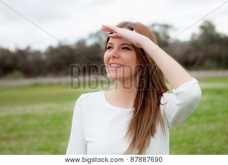 Beautiful young woman looking at side in the meadow
