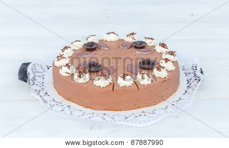 Chocolate Cream Cake On White Wood With Cake Lace