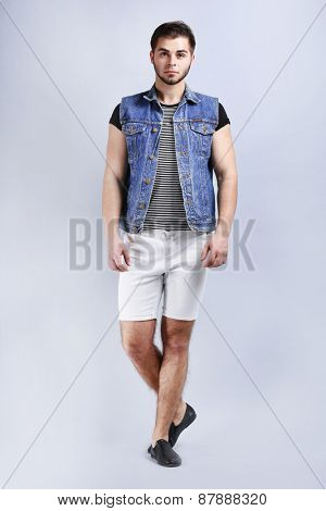 Man in white shorts and jeans vest on gray background