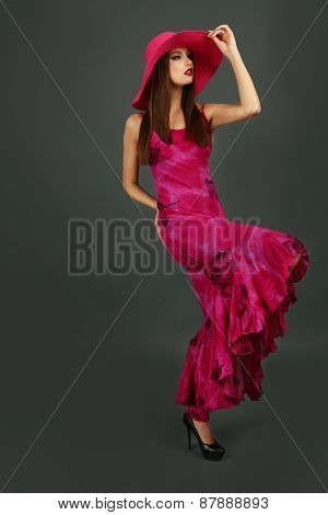 Beautiful young woman in long pink dress and hat on dark gray background