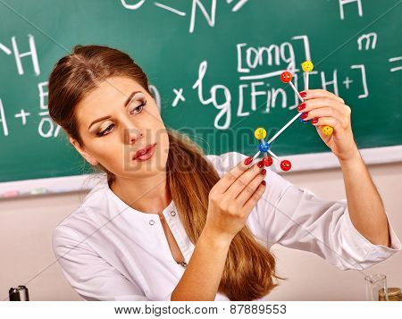 Chemistry teacher with test-tube at classroom.