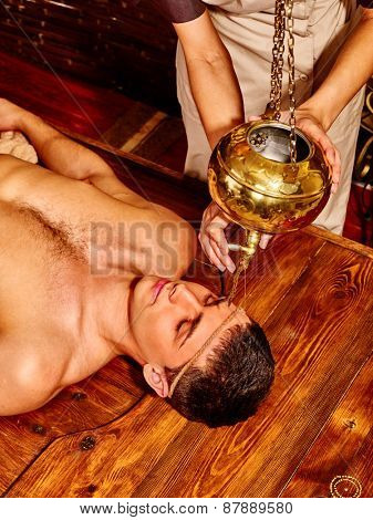 Young man having Ayurveda spa treatment.