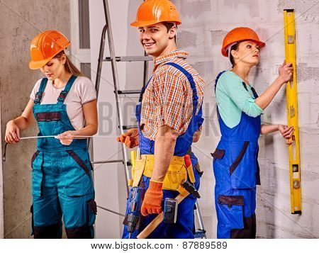 Happy group people in builder uniform indoor.